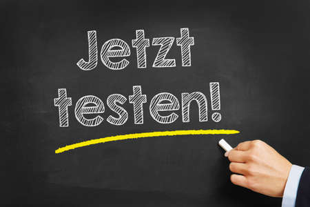 probation: Hand with chalk writing in German Jetzt testen! (test it now) on a chalkboard