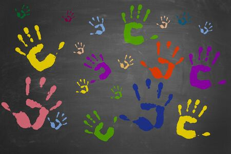 kids painted hands: Many different colorful hand prints on a blackboard Stock Photo