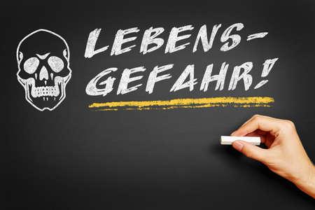 mortal danger: Hand with chalk writing in German Lebensgefahr! (Mortal danger) on a blackboard Stock Photo