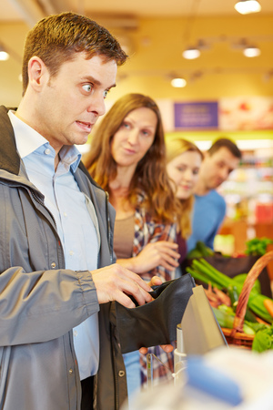 line up: Embarrassed man at supermarket checkout forgot his money for payment