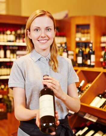 recommending: Smiling sommelier in wine shop recommending bottle of red wine Stock Photo