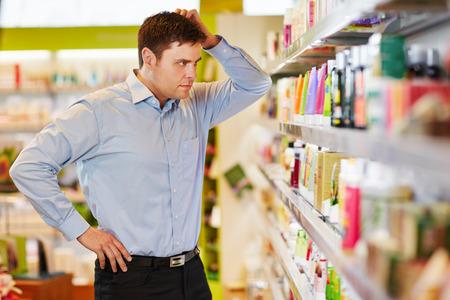 男の持続可能なスーパー ドラッグ ストアで買い物をする