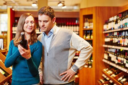 buy: Couple shopping for bottle of red wine in a beverage market