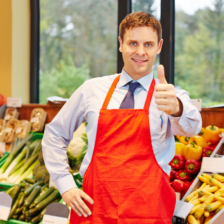 merchant: Smiling happy supermarket employee holding his thumbs up