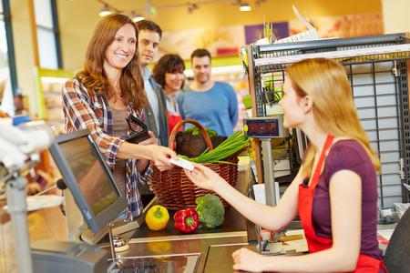 Uśmiechnięta kobieta z jej karty płatnicze w supermarkecie WE kasie