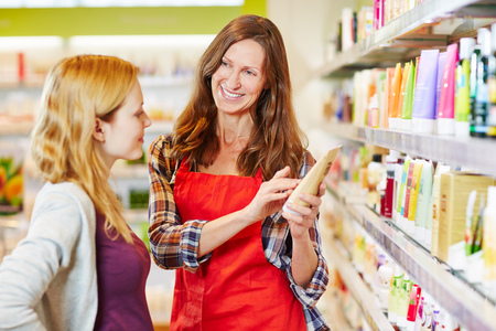 skin care products: Woman in drugstore gets advice from saleswoman while shopping for cosmetics Stock Photo