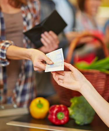 Hands doing payment with cash money at supermarket checkout