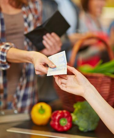 Mani che fanno il pagamento con denaro contante in cassa supermercato