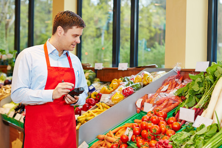 merchant: Store manager in supermarket ordering fresh vegetables with mobile data registration terminal