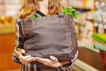 cart: Woman carrying a shopping basket full of fresh vegetables in a supermarket Stock Photo