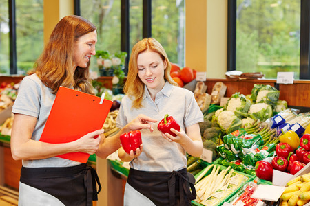 health food store: Salesclerk in training getting help from staff in a supermarket Stock Photo