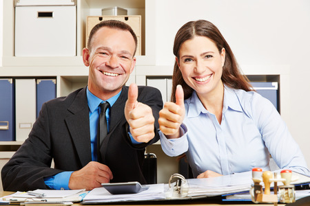 tax consultants: Two happy business people in office holding their thumbs up