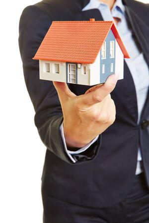 bienes raices: Las manos de un agente de bienes raíces femenina que sostiene una pequeña casa como concepto para un hogar