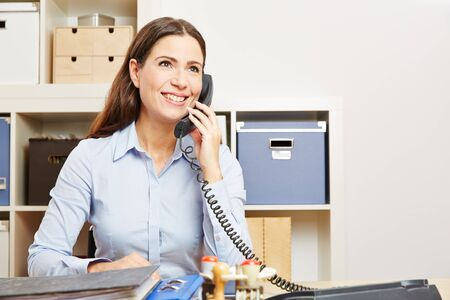 service desk: Smiling business woman making a phone call in the office to a customer support hotline Stock Photo