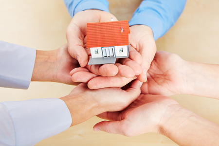 household insurance: Many hands holding together a small house as concept for security and protection