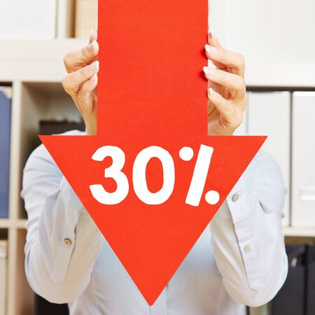 discount: Red arrow with 30% discount being held by female hands Stock Photo
