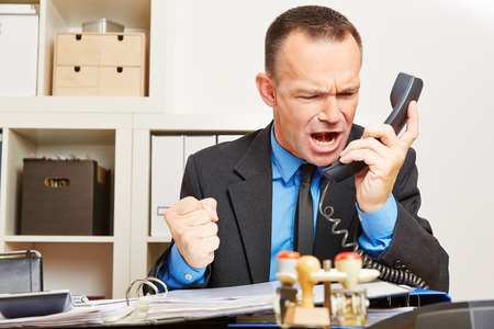 choleric: Angry business man screaming at phone in his office
