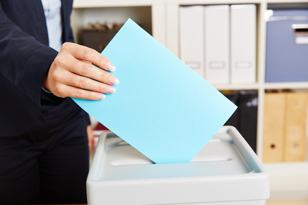 Woman voting with ballot paper on box during election