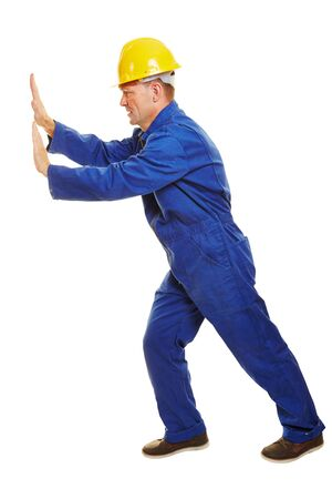 boiler suit: Isolated full body construction worker with safety helmet pushing boundary to the side