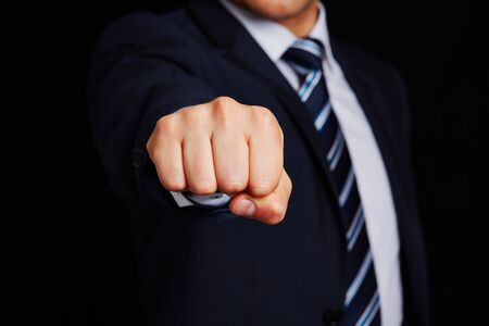 clenched fist: Business manager with clenched fist on dark background