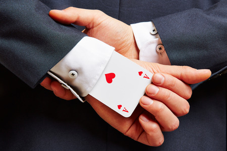 magic trick: Business man with ace in his sleeve and arms on the back Stock Photo