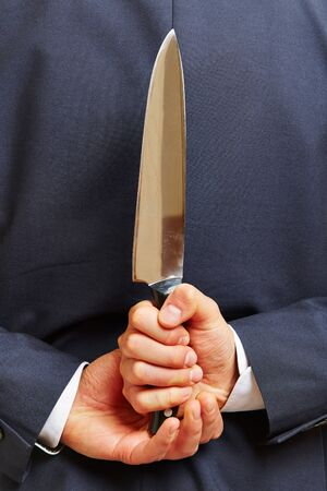 treacherous: Hand of a business man holding a big knife behind his back Stock Photo