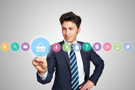 web shopping: Business man choosing shopping cart icon for online shopping on a touchscreen