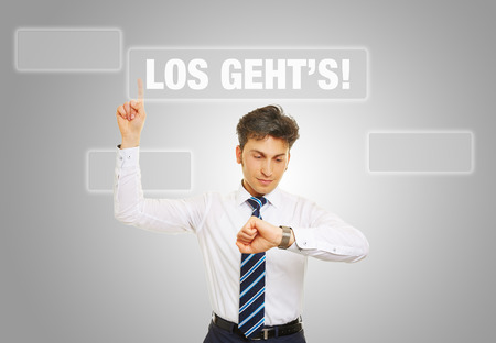 restart: Business man pressing German slogan Los gehts (lets go) while checking his watch Stock Photo