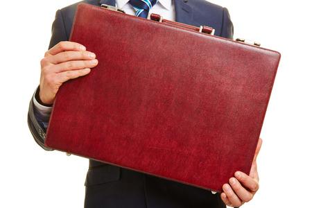 Handen van een zakenman die een rode leren aktetas