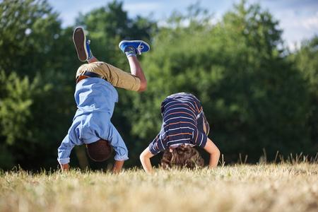 Zwei Jungen machen einen Purzelbaum und Spaß im Park