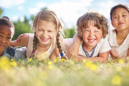 Interraciale groep kinderen in de zomer op het gras