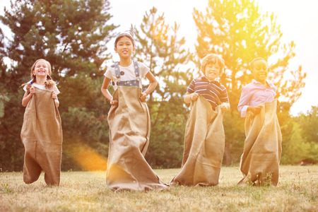 Interracial group of children competing in a sack race at the park
