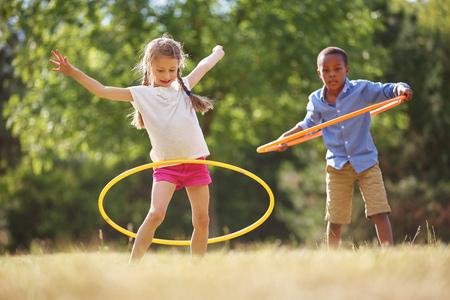 Ragazza e ragazzo con il cerchio di hula giocare al parco