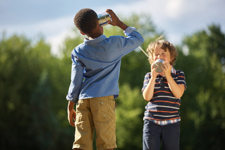 tin can telephone: Two boys playing tin can telephone and having fun at the park Stock Photo