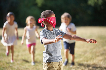 buff: Group of children plays blind mans buff at the park in summer