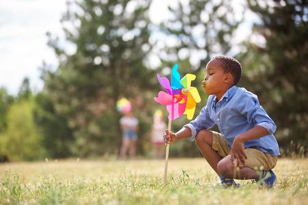 African boy blows at his pinwheel and plays Stock Photo