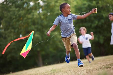 papalote: niño africano que se divierte volando una cometa en la naturaleza Foto de archivo