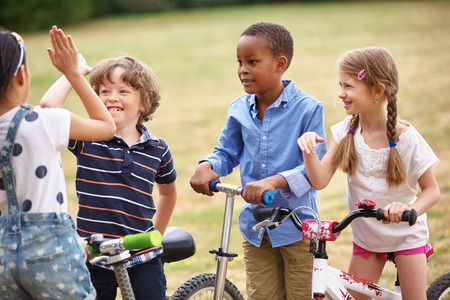 high society: Happy Children in a team making a high five sign Stock Photo