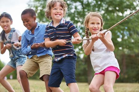 Groep kinderen trekken een touw in het park Stockfoto