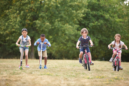 mountainbike: Children with mountainbike and scooter racing at the park Stock Photo