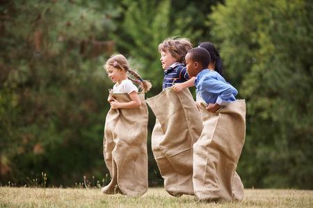 razas de personas: Grupo interracial de niños que compiten en una carrera de sacos en verano