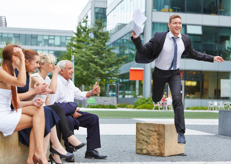 business obstacle: Team cheering for business man jumping over an obstacle for motivation