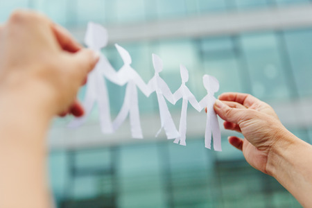 team hands: Two hands holding a business team made of paper cut-outs Stock Photo