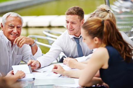 personas reunidas: Equipo de negocios exitosos haciendo la planificación de una reunión al aire libre en una mesa