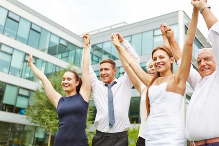 Equipo de negocios que anima feliz que sostiene juntas las manos en alto