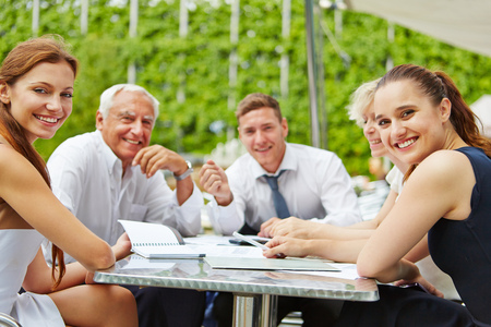 staff: Successful business people sitting outdoors on a table and working Stock Photo
