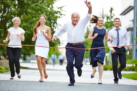 Senior manager gejuich bij het nemen van leiderschap in een business race naar de finish Stockfoto