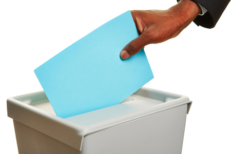 African Hand mit Stimmzettel in Wahlurne im Wahl