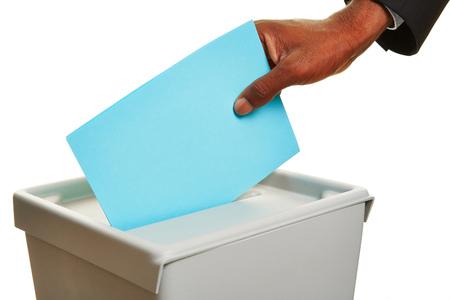 mano africana con scheda di voto in urne durante le elezioni