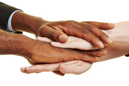 African and caucasian hands stacked as symbol for teamwork Stock Photo